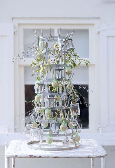 flessenrek opgetuigd met vetbollen, glazen windlichtjes en mistletoe. Op de buitentafel voor het raam.