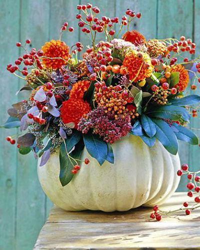 boeket met rozenbottels, dahlia's en laurierkers in uitgeholde pompoen als vaas
