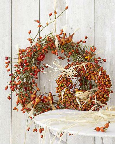 Kransen en boeketten maken met rozenbottels, versierd met kerstboomvogeltjes en raffia