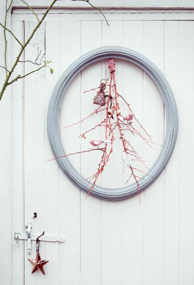 takken versieren: ondersteboven gehangen in ovale lijst tegen wand