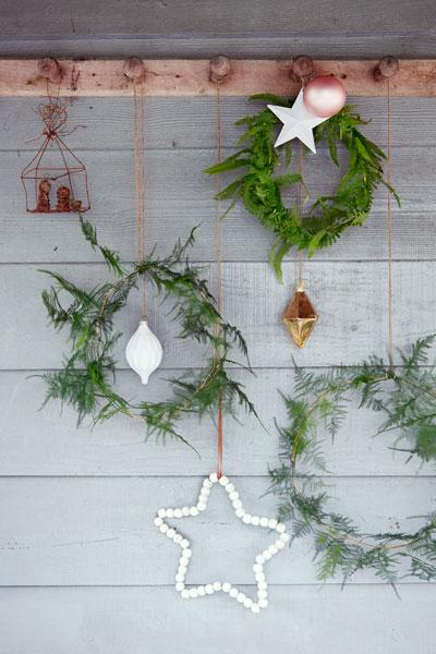 takken versieren: kerstkransen van varentakken tegen houten schutting
